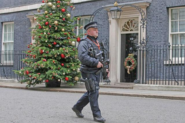 An armed police carries his automatic weapon as he walks on patrol outside 10 Downing Street in central London on Wednesday