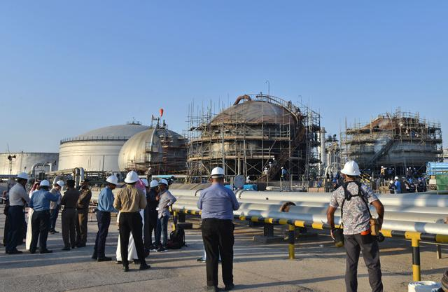 Journalists gather next to a damaged installation in Saudi Arabia's Abqaiq oil processing plant on Friday