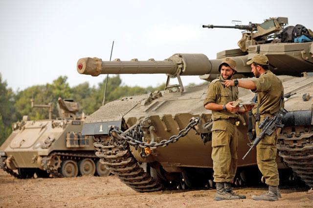 Israeli forces stand next to a tank as armoured vehicles gather in an open area near the border with the besieged Gaza Strip on Thursday