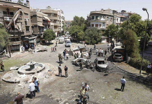 Syrians gather to inspect the damage at the site of a suicide bomb attack in the capital Damascus' eastern Tahrir Square district on Sunday