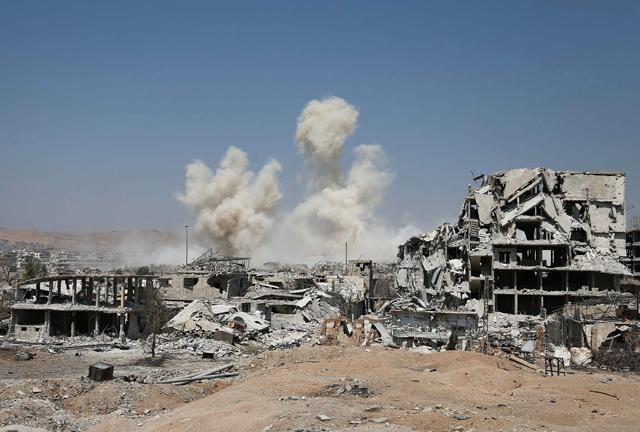 Smoke rises from buildings following a strike on a rebel-held area of the Jobar district east of the Syrian capital on Thursday