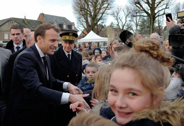 French President Emmanuel Macron shakes hands with residents before visiting a migrant centre in Croisilles northern France on Tuesday