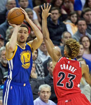 380514ee4b06 Golden State Warriors  guard Klay Thompson shoots a three- point basket  over Portland Trail Blazers  forward Allen Crabbe during their NBA  basketball game ...